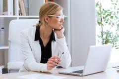 Bella giovane donna di affari che sembra obliqua mentre lavorando con il suo computer portatile nell'ufficio Fotografie Stock