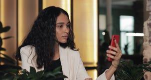 Bella giovane donna di affari che si siede nell'ufficio moderno e che parla con la video-chiacchierata in smartphone archivi video