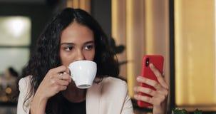 Bella giovane donna di affari che si siede in ufficio o caffè moderno e che parla con la video-chiacchierata in smartphone Ride video d archivio