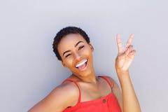 Bella giovane donna di colore che sorride con il segno della mano di pace fotografia stock