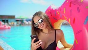 Bella giovane donna di estate con lo smartphone Ragazza del bikini che per mezzo del telefono dallo stagno Donna che texting sul  video d archivio