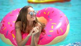 Bella giovane donna di estate Ragazza del bikini che si rilassa dentro in galleggiante spruzzato della ciambella allo stagno, vac video d archivio