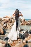 Bella giovane donna di stile di boho in vestito bianco che sta sullo ston Fotografia Stock