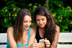 Bella giovane donna due che passa in rassegna sullo Smart Phone Fotografia Stock Libera da Diritti