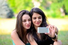 Bella giovane donna due che prende la loro foto in parco Immagine Stock Libera da Diritti