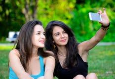 Bella giovane donna due che prende la loro foto in parco Fotografia Stock Libera da Diritti