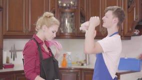 Bella giovane donna e un uomo in grembiuli che decolla i guanti ed alti cinque La famiglia che finisce la pulizia della casa stock footage