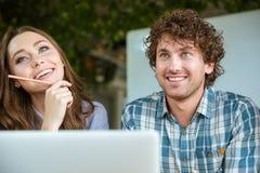 Bella giovane donna ed uomo bello che per mezzo del computer portatile Fotografia Stock
