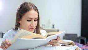 Bella giovane donna europea che gode del fine settimana che legge libro interessante a casa stock footage