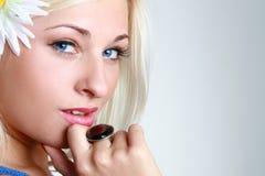 Bella giovane donna eyed blu con il fiore Immagini Stock