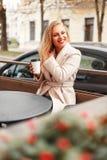 Bella giovane donna felice in cappotto d'avanguardia con seduta del caffè immagini stock