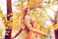 Bella giovane donna felice che cammina nel parco di autunno Fotografia Stock