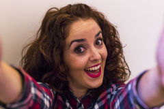 Bella giovane donna felice che prende un selfie sopra backgroun bianco Fotografia Stock