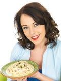 Bella giovane donna felice che tiene un piatto della pasta di Carbonara degli spaghetti Fotografia Stock