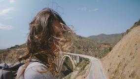 Bella giovane donna felice con sorridere dei capelli di volo, posante alla macchina fotografica al punto di osservazione al ponte video d archivio