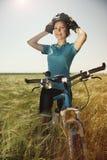 Bella giovane donna felice con una bici su un campo che tiene la sua h fotografia stock libera da diritti