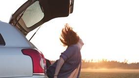 Bella giovane donna felice e che balla in un tronco dell'automobile durante il viaggio stradale in Europa negli ultimi verbali de archivi video