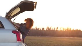 Bella giovane donna felice e che balla in un tronco dell'automobile durante il viaggio stradale in Europa negli ultimi verbali de video d archivio