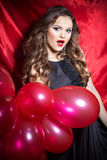 Bella giovane donna felice elegante con le palle rosse in mani con rossetto rosso immagine stock
