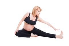 Bella giovane donna incinta che allunga sul pavimento Immagine Stock