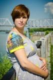 Bella giovane donna incinta dall'argine, vicino al fiume Fotografia Stock Libera da Diritti