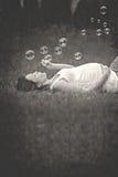 Bella giovane donna incinta, riposandosi nell'erba, facente fotografia stock