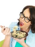 Bella giovane donna ispana felice che mangia un piatto di linguine vegetariano con spinaci ed i funghi immagine stock libera da diritti