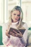 Bella giovane donna in maglione rosa che legge un libro Fotografia Stock