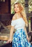 Bella giovane donna in maxi gonna floreale che cammina nel giardino di fioritura della molla fotografia stock libera da diritti