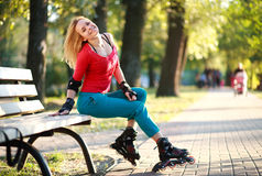 Bella giovane donna nei pattini di rullo che si siedono sul banco di parco fotografia stock libera da diritti