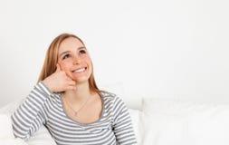 Bella giovane donna nei sogni su un sofà Immagini Stock Libere da Diritti