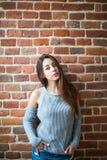 Bella giovane donna nel sorridere di abbigliamento casual, stante contro il muro di mattoni bianco Fotografia Stock Libera da Diritti