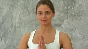 Bella giovane donna nell'yoga di pratica degli abiti sportivi ed esaminare macchina fotografica mentre sedendosi nella posizione  video d archivio