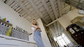 Bella giovane donna nella cucina azione Ritratto della bionda adorabile adorabile con la maglietta bianca vestita dei capelli lun stock footage