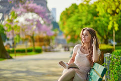 Bella giovane donna nella lettura di Parigi sul banco all'aperto fotografia stock