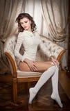 Bella giovane donna nella seduta bianca sul sofà che posa provocatorio nel paesaggio del boudoir. Ragazza castana attraente con ca immagini stock libere da diritti