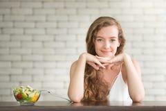 Bella giovane donna nelle posizioni allegre con l'insalatiera immagini stock