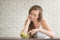Bella giovane donna nelle posizioni allegre con l'insalatiera fotografie stock