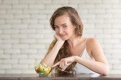 Bella giovane donna nelle posizioni allegre con l'insalatiera fotografia stock