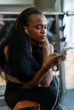 Bella giovane donna nera con capelli lunghi di lusso che mandano un sms sul suo smartphone nella palestra Fotografia Stock Libera da Diritti