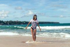 Bella giovane donna in occhiali da sole che posano sulla spiaggia di un'isola tropicale di Bali, Indonesia Fotografia Stock