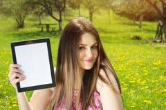 Bella giovane donna in parco che mostra il computer della compressa Fotografie Stock Libere da Diritti