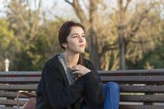 Bella giovane donna pensierosa nel distogliere lo sguardo del parco Fotografia Stock Libera da Diritti