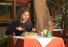 Bella giovane donna peruviana che mangia pizza in una r Immagini Stock Libere da Diritti