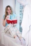 Bella giovane donna in pigiami che si siedono dalla finestra con il libro Immagine Stock