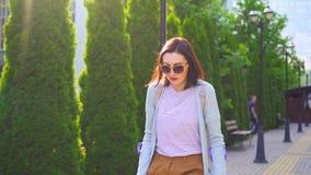 Bella giovane donna positiva alla moda con la lesione sulle grucce che cammina giù la via soleggiata archivi video