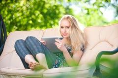 Bella giovane donna positiva che per mezzo del ridurre in pani Immagini Stock