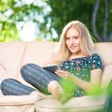 Bella giovane donna positiva che per mezzo del ridurre in pani Fotografia Stock Libera da Diritti