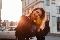 Bella giovane donna positiva graziosa in una maglietta alla moda nei supporti e nelle risate bianchi dei jeans vicino alle costru fotografia stock libera da diritti