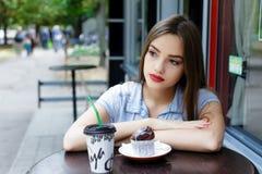 Bella giovane donna premurosa in caffè all'aperto con caffè Fotografie Stock